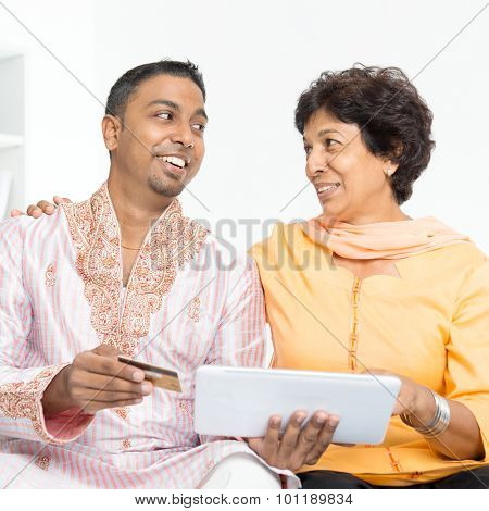 Portrait of Indian family using internet payment at home. Mature 50s Indian woman and 30s grown son happy online shopping with credit card.