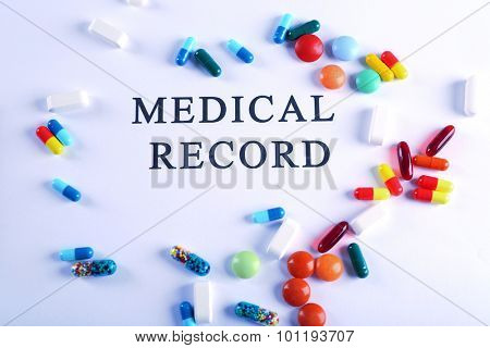 Inscription MEDICAL RECORD and pills isolated on white
