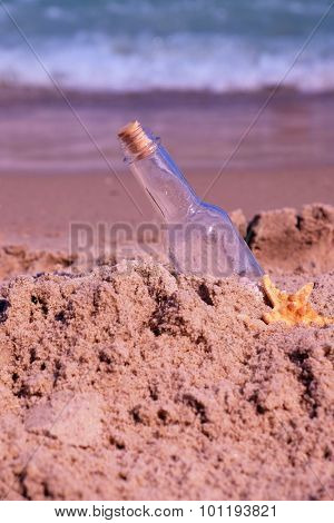 Message in bottle on sand on sea background