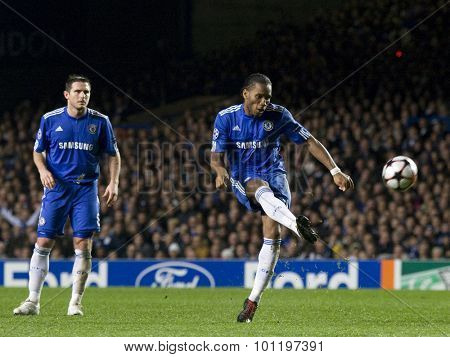 LONDON, ENGLAND. 08 December 2009. - Frank Lampard playing for Chelsea  watches on as Didier Drogba playing for Chelsea takes a free kick during the Uefa Champions League match