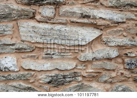 Grey wall of stone damaged by the passage of time