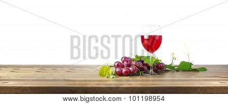 Red wine glass and bunch of grapes on wooden table