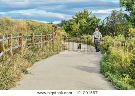 WINDSOR, CO, USA, SEPTEMBER 5, 2015: Morning walk with a dog on Poudre River Trail - paved bike trail extending more than 20 miles between Timnath and Greeley.