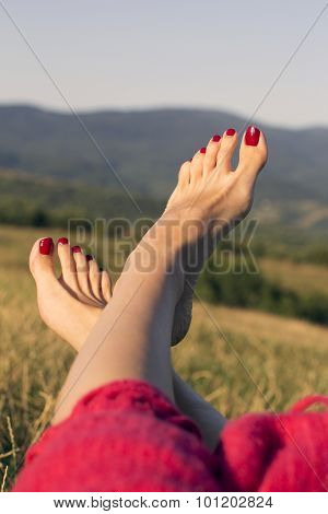 The Female Feet With Red Nails On The Mountains  Background