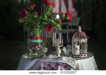 Table Decorated With A Vase Of Flowers, Candlesticks And Decorative Cage