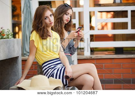 Two happy girlfriends view photos on a mobile phone