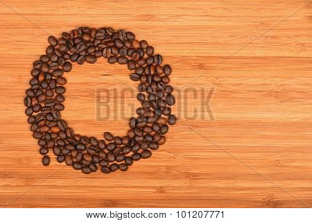 Circle Shaped Coffee Beans Over Bamboo Wood Background