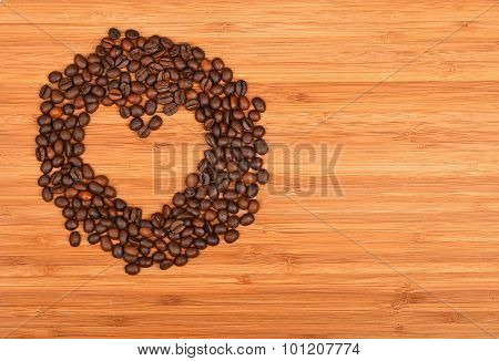 Heart Shaped Coffee Beans Frame Over Bamboo Wood Background