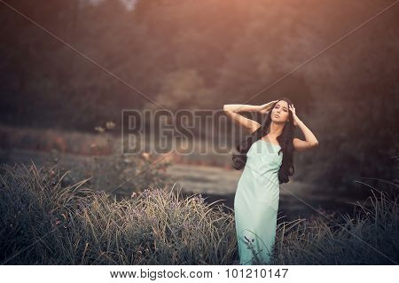 Fantasy fairytale, beautiful but sad woman - wood nymph among tall grass and rays of sun. Outdoor