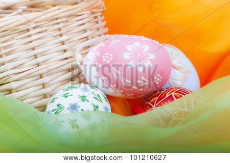 Close-up of strawy basket with Easter eggs and velvet