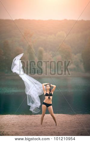 Young sexy woman in underwear on beach at summer day with large veil