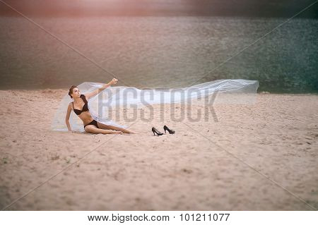 Young sexy woman in lingerie on beach at summer day with large veil