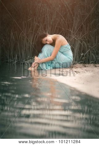 Charming, romantic girl sleeping and dreams near the water stream. Outdoor