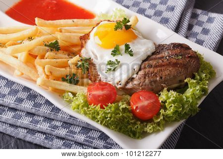 Beefsteak With Fried Egg And Fries On A Plate Closeup. Horizontal
