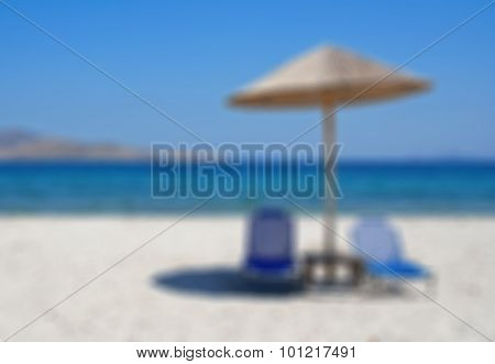 Greece. Kos Island. Two Chairs And Umbrella On The Beach. In Blur Style