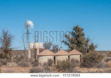 Rondavels Next To A Windpump And Water Storage Tanks
