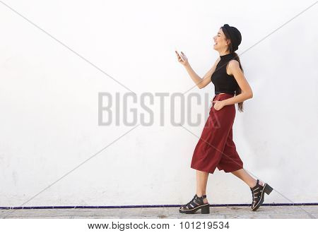 Smiling Teen Walking And Looking At Mobile Phone