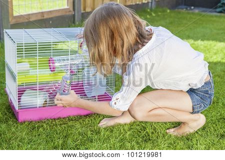 Girl in the backyard playing with the hamster in cage