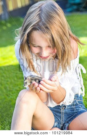 School girl sitting in the backyard with a small hamster in palms