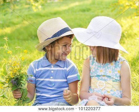 Boy and girl in hats looking at each other