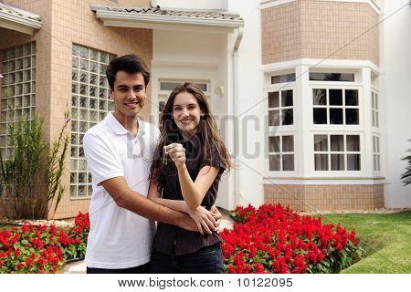Propietarios felices delante de casa nueva