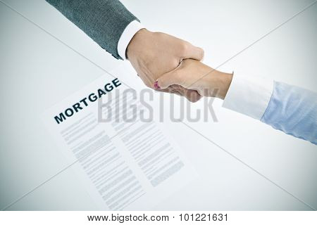 closeup of a young man and a young woman shaking hands above a table with a mortgage loan document, slight vignette added