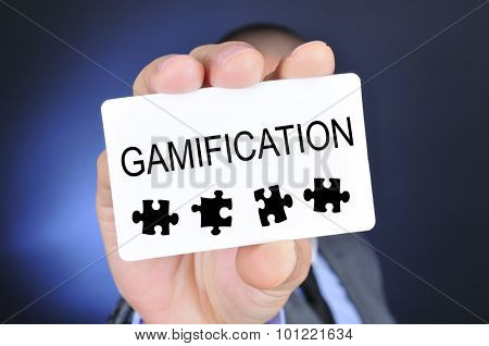 young caucasian man in suit shows a signboard with the word gamification written in it