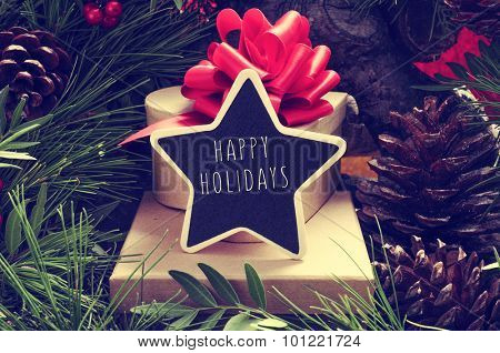 a star-shaped chalkboard with the text happy holidays on a pile of gift boxes placed under the christmas tree and surrounded by natural ornaments such as pine cones
