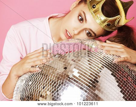 young cute girl like barbie on pink background with disco ball and crown