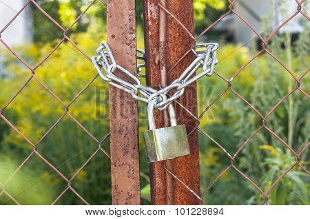 Rusted gate is lock with a chain and padlock