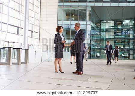 Two senior colleagues talking in the foyer of a big business