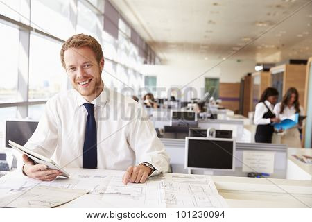Young architect at work in an office, smiling to camera