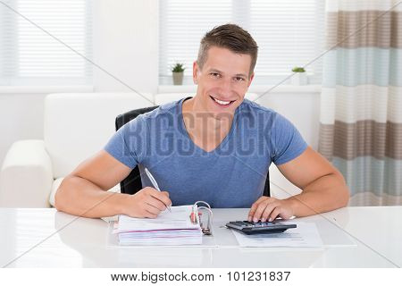 Man Doing Calculation At Home