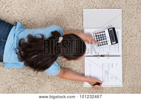 Woman On Carpet Calculating Finance
