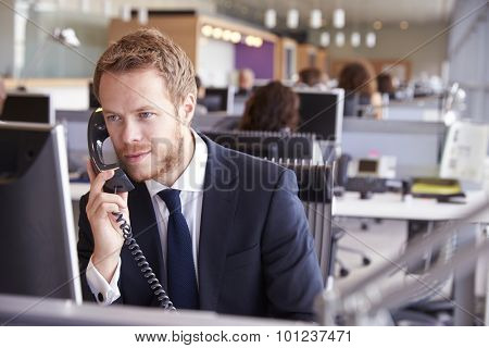 Young businessman at work in a busy, open plan office
