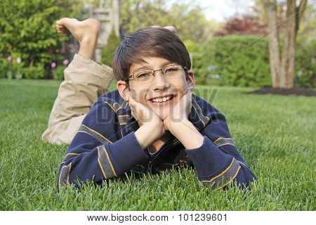 Young boy laying in grass leaning on hands