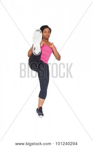 Fit woman kicking to camera on white background