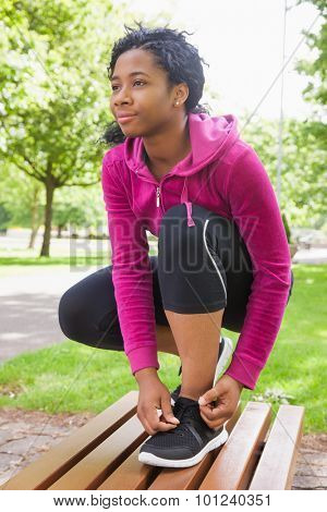 Hipster tying her shoelace in the park