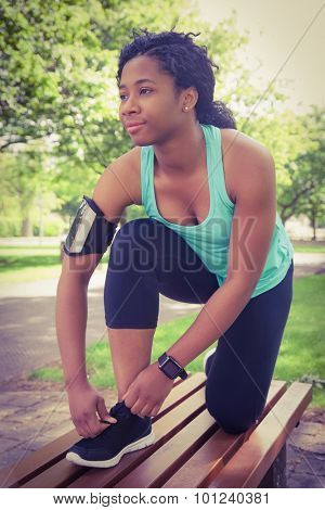 Fit woman tying her shoelace i n the park