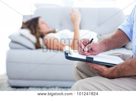 Therapist writing on notepad with female patient in background
