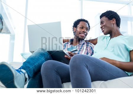 Man with laptop and credit card sitting by wife on sofa