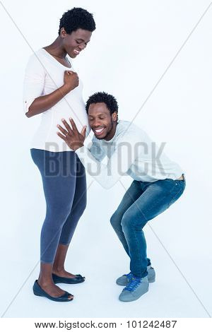 Happy husband with closed eyes listening to his pregnant wife belly against white background