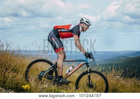 old racer on mountain bike downhill