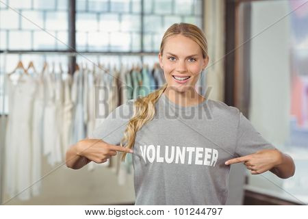 Portrait of happy woman showing volunteer text on tshirt in office