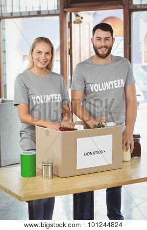 Happy man and woman separating donation stuffs in creative ofice