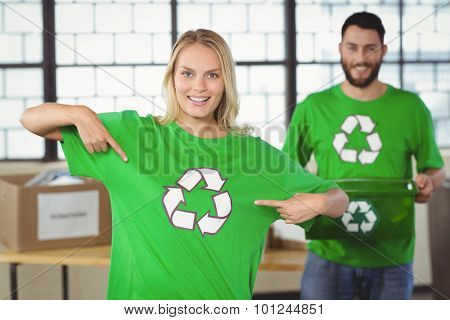 Portrait of woman pointing towards recycling symbol on tshirts with colleague in background