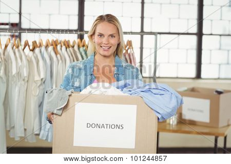 Portrait of cheerful woman volunteer holding clothes donation box