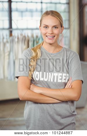 Portrait of beautiful smiling woman with arms crossed standing in creative office