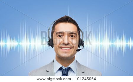business, people, technology and service concept - smiling businessman in headset over sound wave or signal diagram on blue background