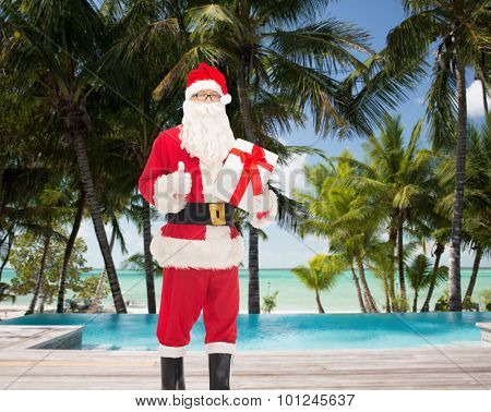 christmas, holidays, travel and people concept - man in costume of santa claus with gift box showing thumbs up gesture over swimming pool on tropical beach background
